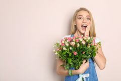 Beautiful young woman with bouquet of roses. On color background Royalty Free Stock Image
