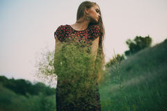 Beautiful young woman with a bouquet of wild flowers Stock Images