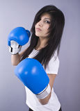 Beautiful young woman with boxing gloves. Portrait of a beautiful young woman with blue boxing gloves stock images
