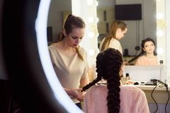 Beautiful Young Woman With Braid Hairstyle. Beautiful woman getting haircut by hairdresser in the beauty salon stock photo