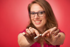 Beautiful young woman breaks a cigarette as a gesture for quit smoking. Smiling for breaking unhealthy habit Stock Image