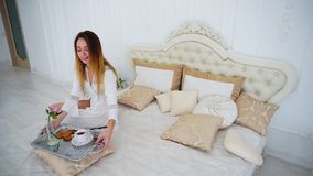 Women Housewife Making Morning Coffee, Comes With Tray in Hands and Sits Down. Beautiful Young Woman Brewed Refreshing Drink, Coffee or Tea and Sits Down on Big Royalty Free Stock Photos