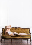 Beautiful young woman in bridal lingerie on a retro sofa Stock Images