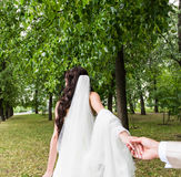 Beautiful young woman bride holds the hand of a man in outdoors. Follow me Royalty Free Stock Photos