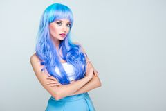beautiful young woman with bright blue hair and crossed arms looking at camera stock image