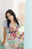 Beautiful young woman in a bright dress sitting on the windowsill Royalty Free Stock Photography