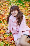 Beautiful young woman on a bright fall day. Sitting on the ground covered with fallen autumn leaves stock photo