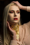 Beautiful young woman with bright makeup and gold foil on her ne Royalty Free Stock Photography
