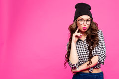 Beautiful young woman with bright makeup and pink lips make a kiss holding your finger near the . Hipster girl in hat Stock Photo