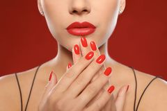 Beautiful young woman with bright manicure on color background. Nail polish trends royalty free stock images