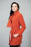 Beautiful young woman in a bright orange coat Royalty Free Stock Photo