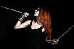 Beautiful young woman with bright red hair and tied arms Stock Images