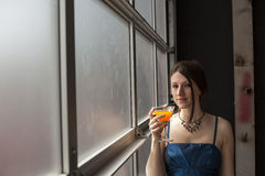 Beautiful Young Woman with Brown Hair Drinking Glass of Mango Ju. Beautiful young woman with brown hair and eyes drinking a glass of mango juice Stock Photos