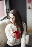 Beautiful Young Woman with Brown Hair and Eyes Drinking Coffee royalty free stock photos