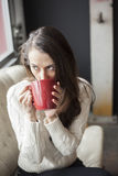 Beautiful Young Woman with Brown Hair and Eyes Drinking Coffee Royalty Free Stock Photo