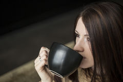 Young Woman with Brown Hair and Eyes Holding Black Cofee Cup Stock Image