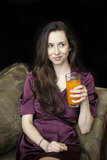 Beautiful Young Woman Holding Glass of Mango Juice. Beautiful young woman with brown hair and eyes holding a glass of mango juice royalty free stock photo