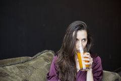 Beautiful Young Woman Holding Glass of Mango Juice. Beautiful young woman with brown hair and eyes holding a glass of mango juice royalty free stock photography