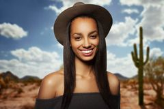 Beautiful young woman with brown hat, long hair, smiling, with naked shoulders, isolated on a blurry desert background. stock photography