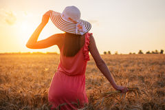 Beautiful young woman with brown hear wearing rose dress and hat enjoying outdoors looking to the sun on perfect wheat field on su Stock Images