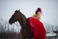 Beautiful young woman with a brown horse. Beautiful woman in red dress with a brown horse stock photo