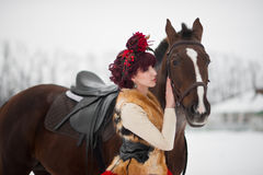 Beautiful young woman with a brown horse. Beautiful woman in red dress with a brown horse stock photos