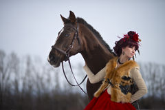 Beautiful young woman with a brown horse. Beautiful woman in red dress with a brown horse royalty free stock photography