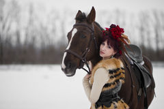 Beautiful young woman with a brown horse. Beautiful woman in red dress with a brown horse stock photography