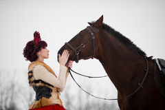 Beautiful young woman with a brown horse. Beautiful woman in red dress with a brown horse stock image