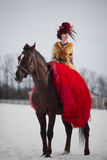 Beautiful young woman with a brown horse. Beautiful woman in red dress with a brown horse stock images