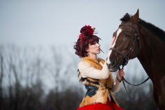 Beautiful young woman with a brown horse. Beautiful woman in red dress with a brown horse royalty free stock images