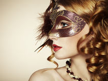 Beautiful young woman in brown venetian mask Stock Photos