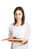 Beautiful young woman browsing through book Stock Photography