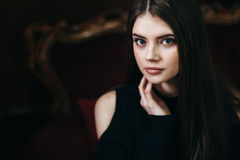 The beautiful young woman the brunette. Sits on a sofa back in a classical interior Royalty Free Stock Photography