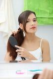 Beautiful young woman brushing her hair Stock Photos