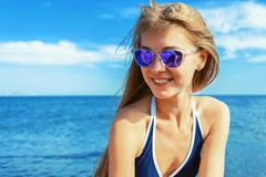 Beautiful young woman in swimsuit at the beach smiling on a sunny day royalty free stock photo