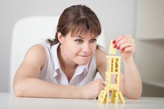 Beautiful young woman builds tower of dominoes Royalty Free Stock Image