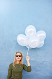 Beautiful young woman with bunch of balloons Royalty Free Stock Image