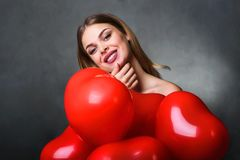 Beautiful young woman with bunch of red heart balloons royalty free stock photos