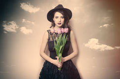 Beautiful young woman with bunch of tulips on the wonderful blue Royalty Free Stock Images