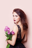 Beautiful young woman with bunch of tulips on the wonderful pink Royalty Free Stock Photography