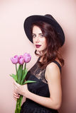 Beautiful young woman with bunch of tulips on the wonderful pink Royalty Free Stock Photo