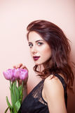 Beautiful young woman with bunch of tulips on the wonderful pink Stock Photography