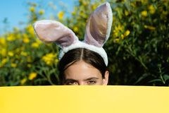 Beautiful young woman with bunny ears and blank poster on outdoor background. Copy space. Easter holiday concept. Discount stock images