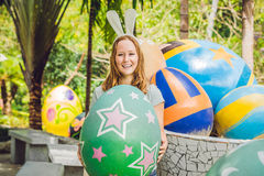 Beautiful young woman with bunny ears having fun with traditional Easter eggs hunt, outdoors. Celebrating Easter holiday Stock Photography
