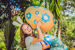 Beautiful young woman with bunny ears having fun with traditional Easter eggs hunt, outdoors. Celebrating Easter holiday Stock Photo