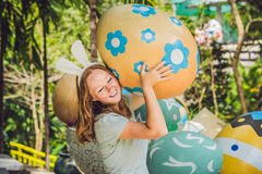 Beautiful young woman with bunny ears having fun with traditional Easter eggs hunt, outdoors. Celebrating Easter holiday Royalty Free Stock Image