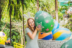 Beautiful young woman with bunny ears having fun with traditional Easter eggs hunt, outdoors. Celebrating Easter holiday Royalty Free Stock Photo