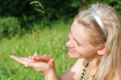 Beautiful young woman and butterfly in green field Stock Photography