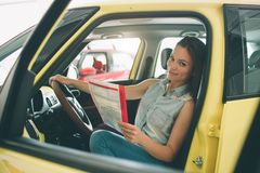 Beautiful young woman buying a car at dealership. Female model sitting Sits in the car interior. Beautiful young women buying a car at dealership. Female model Royalty Free Stock Image